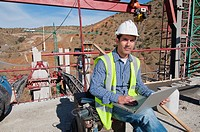 Hispanic construction worker using laptop at construction site