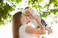 Caucasian woman holding baby girl outdoors
