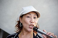 A singaporean woman singing under Esplanade bridge  Singapore