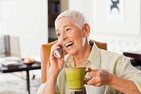 Caucasian woman talking on cell phone and drinking coffee