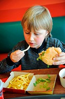Stock photo of an 11 year old boy eating fast food in a restaurant
