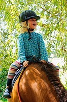 Stock photo of a 6 year old girl riding a pony