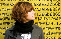 A face of young woman in front of numbers, letters, symbols, background is a painted wall of one of buildings in Geneva, Switzerland
