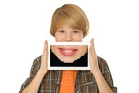 Eleven year old boy is holding a tablet computer or e-reader in front of his face  Tablet displays a large pixelated version of his smile