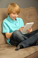 Eleven year old boy using tablet computer or e-reader while sitting on a couch