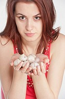 Studio shot of a young woman holding garlic in her hands