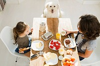 Mother and daughter at table with dog