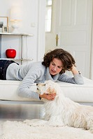 Woman petting dog in living room