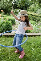 Girl playing with hula hoop in backyard
