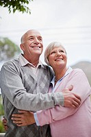 Smiling older couple hugging outdoors