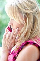 Profile of a 35 year old blond woman talking on a cell phone with hand on her face