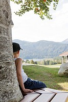 Boy sitting on bench against tree