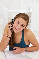 Young teenage girl using a telephone