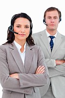 Call center agents with headsets and arms folded against a white background