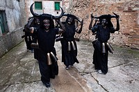 A group of men dressed as devils, parade through the streets of the town