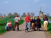 Kids riding horses and bicycle on country road along canal with windmill in Schermerland, Holland                                                     ...