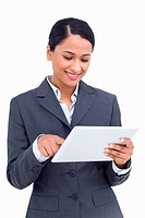 Close up of smiling saleswoman using her tablet computer against a white background