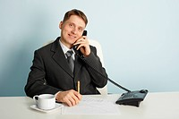 Smiling businessman in talks on phone