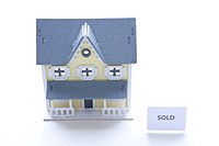 Model of house with sold sign on its sign, high angle view