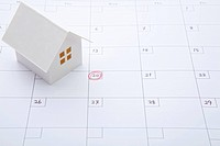 Model of house on calendar with marking on 20th of the month