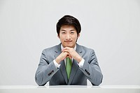 Portrait Of Smiling Asian Businessman Sitting At Desk