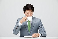 Businessman Sitting At The Desk Drinking Coffee