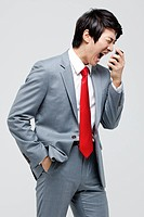 Asian Businessman Shouting Into Cell Phone