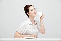 Asian Businesswoman Sitting At A Desk Holding A Cup In Hand