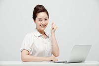 Asian Businesswoman Clenching His Fist Sitting At A Desk With Laptop