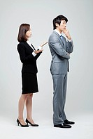 Asian Businesswoman Shrugging On Businessman With Hand On Chin