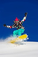 Female snowboarder having fun and riding fast in fresh powder snow