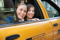 Portrait of two women looking out cab window