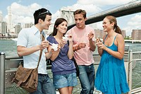 Friends eating ice cream in front of Manhattan skyline, New York City, USA