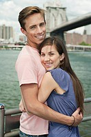 Portrait couple hugging in front of skyline, New York City, USA
