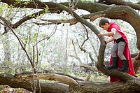 Boy 5_6 in costume standing on log in forest