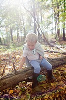 Boy 5-6 in costume sitting on log in forest (thumbnail)