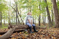 Boy 5_6 in costume sitting on log in forest