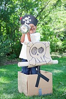 Boy 5_6 wearing pirate costume playing in garden