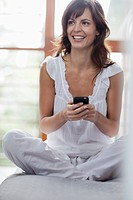 Portrait of smiling woman sitting on bed and using cell phone