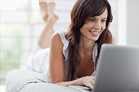 Smiling woman lying on bed and using laptop