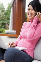 Smiling woman sitting on sofa and using laptop and cell phone