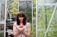 Portrait of mid adult woman in greenhouse holding bowl of ripe tomatoes