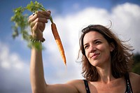 Mid adult woman holding freshly picked carrot against cloudy sky