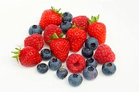 Pile of fresh, juicy, organic strawberries, raspberries and blueberries, on a white background.