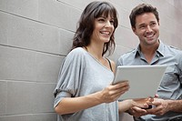 Man and woman using digital tablet and smiling