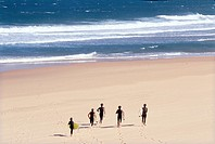 Surfers run across the sand at Guincho, the famous surfing beach, near Lisbon Portugal