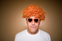 Middle-age man wearing an orange wig and heart-shaped sunglasses