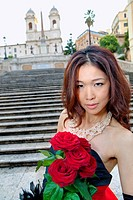 Asian girl with red roses posing on the stairs of Piazza di Spagna Rome Italy