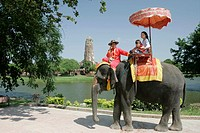 Tourists riding costume elephants view ancient temple site Ayutthaya Thailand