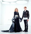 Black haute couture retro futurist couple in modern white hall with vampire inspiration